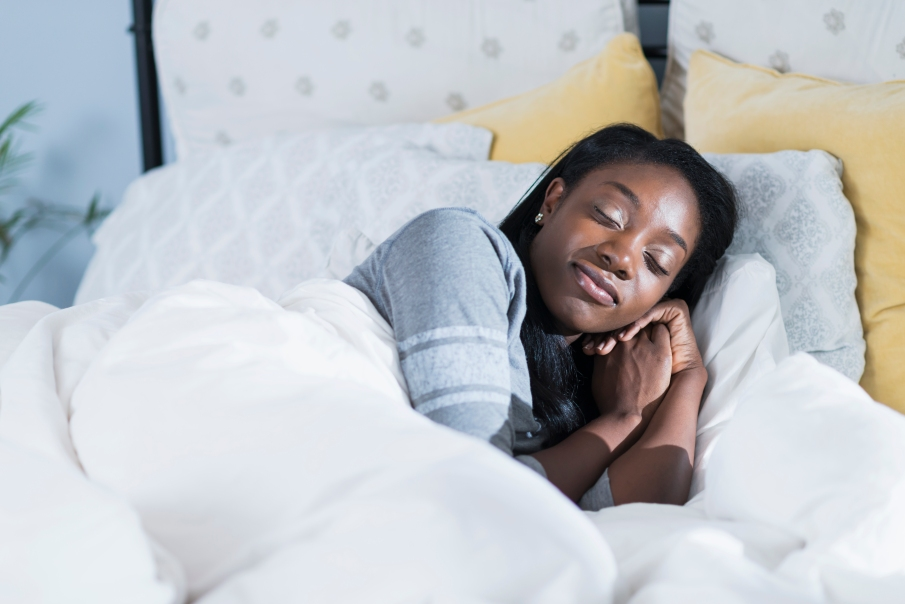 Young African American woman asleep in bed