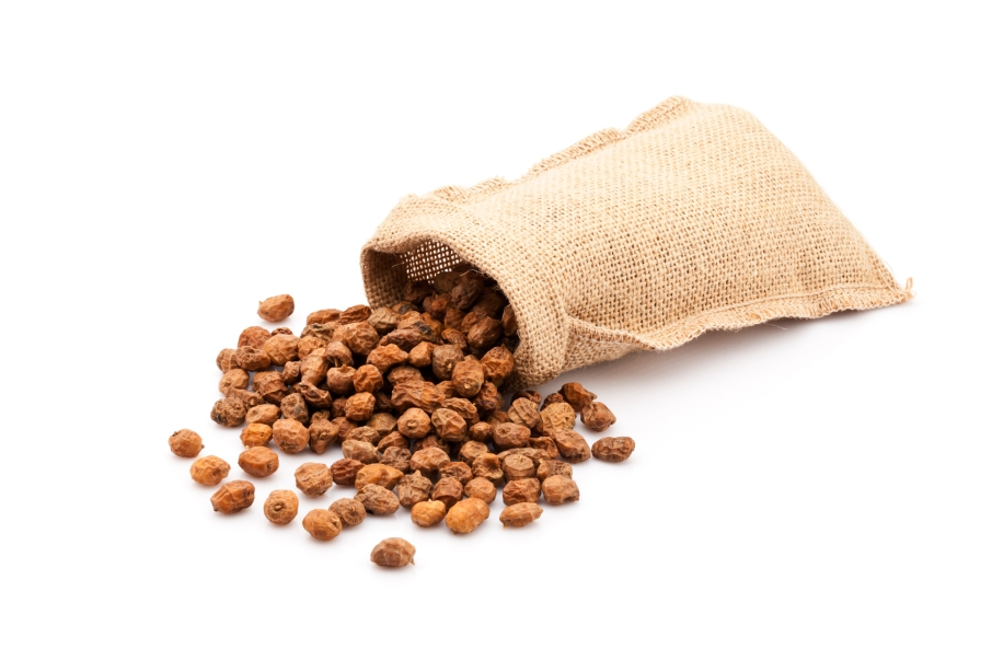 Tigernuts in a burlap sack isolated on white background